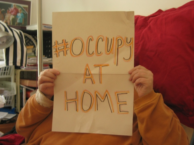 Hand-made sign says #Occupy at Home. It is held in front of the person's face with just their hands and arms visible holding it. It looks as if the person is propped in bed with a red pillow behind them.