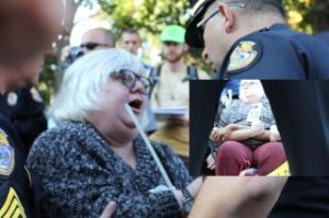 White-haired woman  talking animatedly to two police officers who are putting plastic restraints around her wrists.