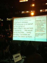 "Image of CART text on a large screen at Occupy Wall Street. Mostly not legible from the picture, but something about ""next Monday would like to be up front,"" is visible."