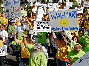 A group of many people standing outside wearing bright yellow or lime green t-shirts, many holding signs. One of the prominent signs has a yellow frowny face in the middle and says, Walmart: Always Low Wages
